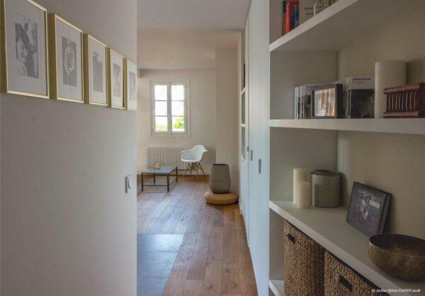 Appartement lumineux et boisé. Le couloir de l'entrée donne sur le salon de la pièce principale. Son mur droit est aménagé avec des étagères sur mesures.