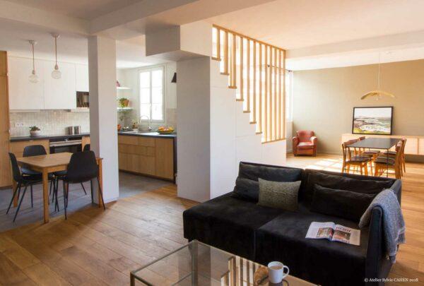 Appartement lumineux et boisé. La Pièce principale est vue du salon. Sur la gauche, on voit l'espace cuisine ouverte avec sa petite table ; au centre l'escalier à barreaudage en chêne ; et au fond la table de la salle à manger.