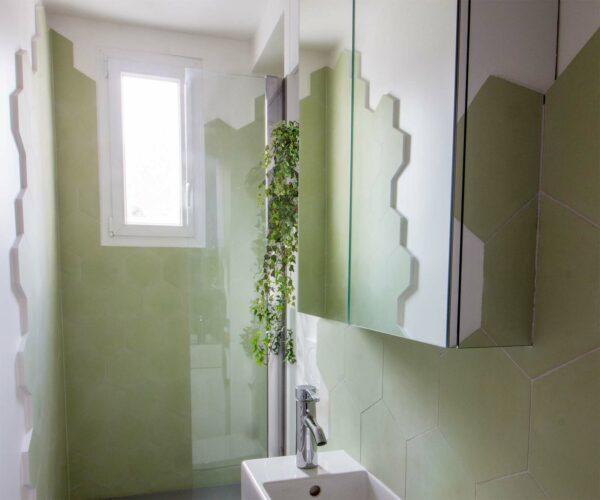 Appartement lumineux et boisé. Les murs de la salle de bain sont composé d'un carrelage hexagonal vert, disposé en carrelage sur une peinture blanche.