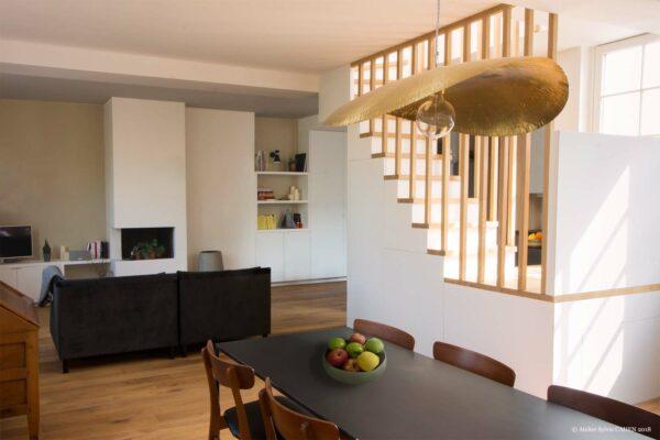 Appartement lumineux et boisé. La Pièce principale est vue de la salle à manger. L'espace salon dispose d'une cheminée et d'un meuble sur mesure.
