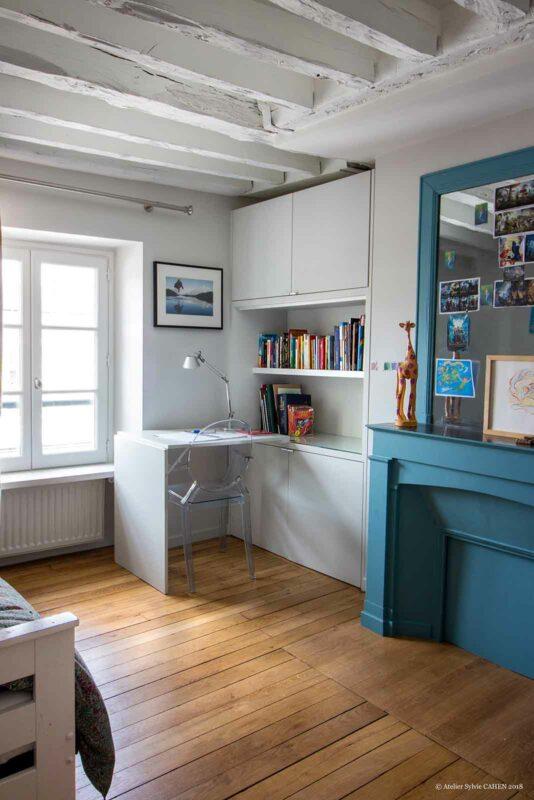 Appartement en structure bois. Chambre avec bureau amovible et cheminée peinte en bleu.