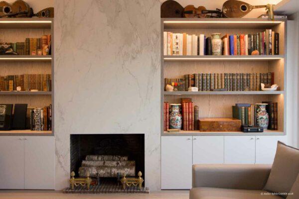 Duplex contemporain. Mur du salon avec cheminée et bibliothèque sur mesure.