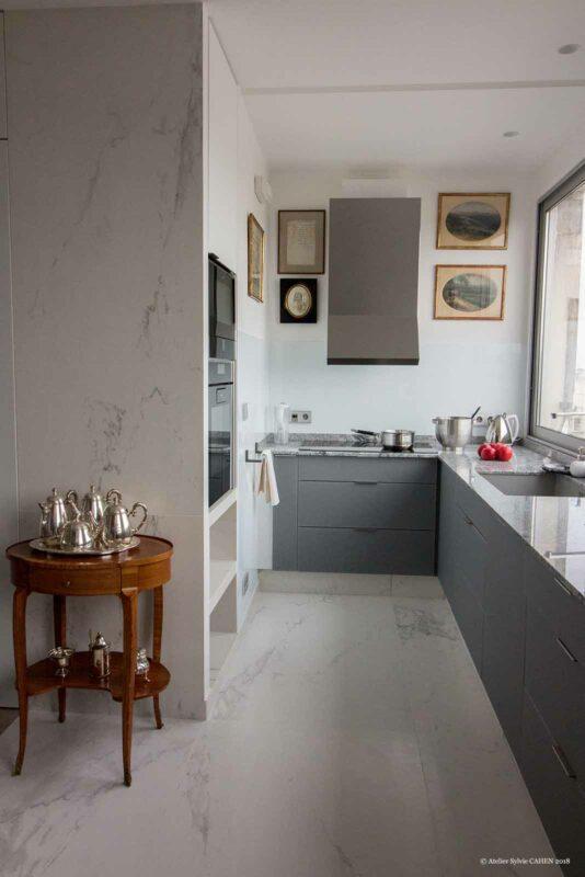 Duplex contemporain. Cuisine ouverte à meubles gris et plan de travail en marbre.