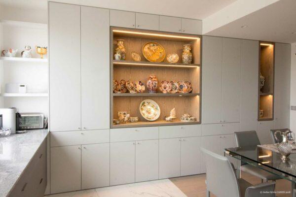 Duplex contemporain. Les murs sont de la salle à manger sont des placards sur mesure blancs et bois. Vue sur la table en verre et chaises en cuir gris et sur la cuisine ouverte.