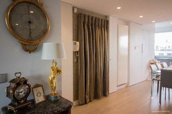 Duplex contemporain. Entrée avec porte habillée d'un rideau. Vue sur la salle à manger.