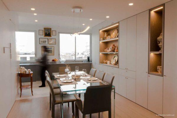 Duplex contemporain. Salle à manger avec table en verre et chaises en cuir gris. Les murs sont des placards sur mesure blancs. Vue sur la cuisine ouverte.