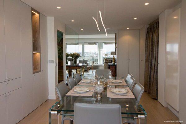 Duplex contemporain. Salle à manger avec table en verre et chaises en cuir gris. Les murs sont des placards sur mesure blancs.
