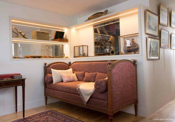 Duplex contemporain. Canapé en coin avec mur à vitrine encastrées.