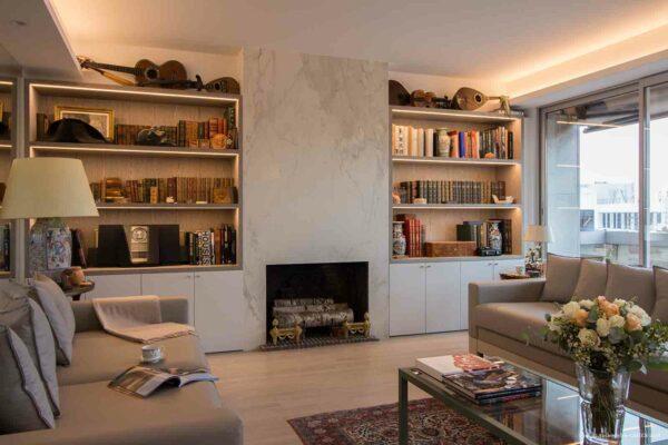 Duplex contemporain. Salon avec canapés en cuirs gris, cheminée et bibliothèque sur mesure.