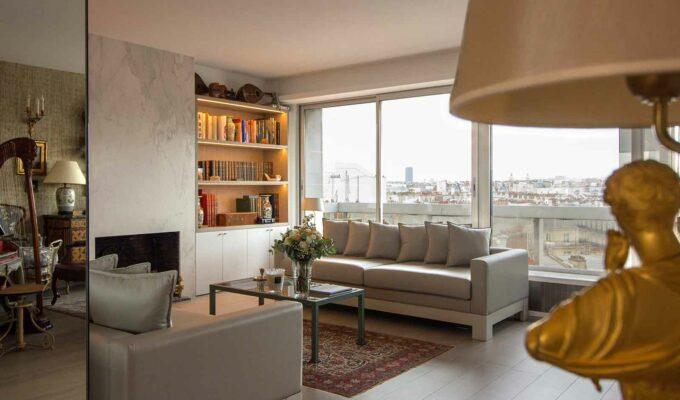 Duplex contemporain. Salon avec canapés en cuirs gris, et baie vitrée donnant sur la terrasse. On aperçoit la cheminée et une bibliothèque sur mesure.