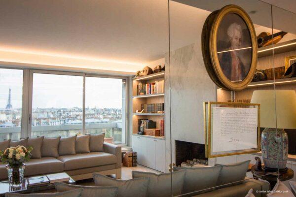 Duplex contemporain. Miroir mural décoré avec un tableau romantique. Vue sur le salon avec canapés en cuirs gris, et la baie vitrée donnant sur la terrasse.