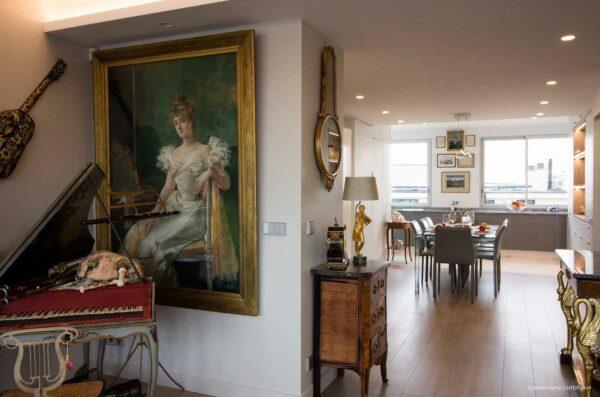 Duplex contemporain. Salon décoré avec tableau romantique et piano ancien. Vue sur la salle à manger avec meubles baroques et objets décoratifs vintages.