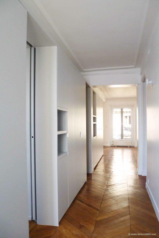 Duplex bleu et jaune. Depuis l'entrée le grand meuble structurant dissimule des passages vers les espaces privés.
