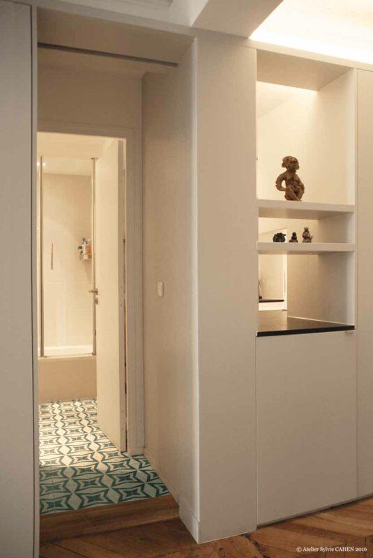 Duplex bleu et jaune. Meuble structurant avec porte et niche ouverte vers la salle de bain.