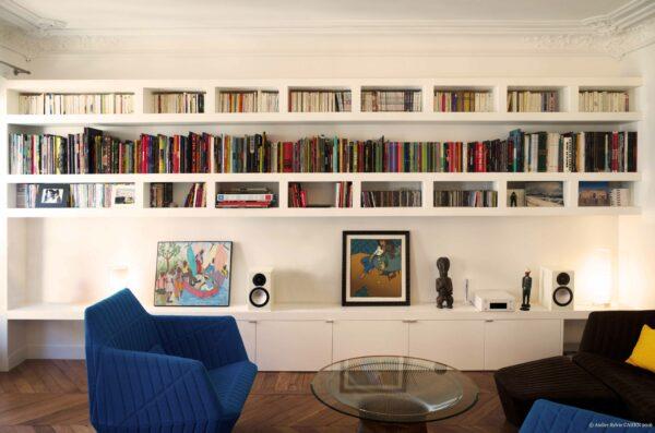 Duplex bleu et jaune. La bibliothèque sur mesure habille tout le mur. Elle reprend le rythme des grilles des bandes dessinées auxquelles elle est destinée.