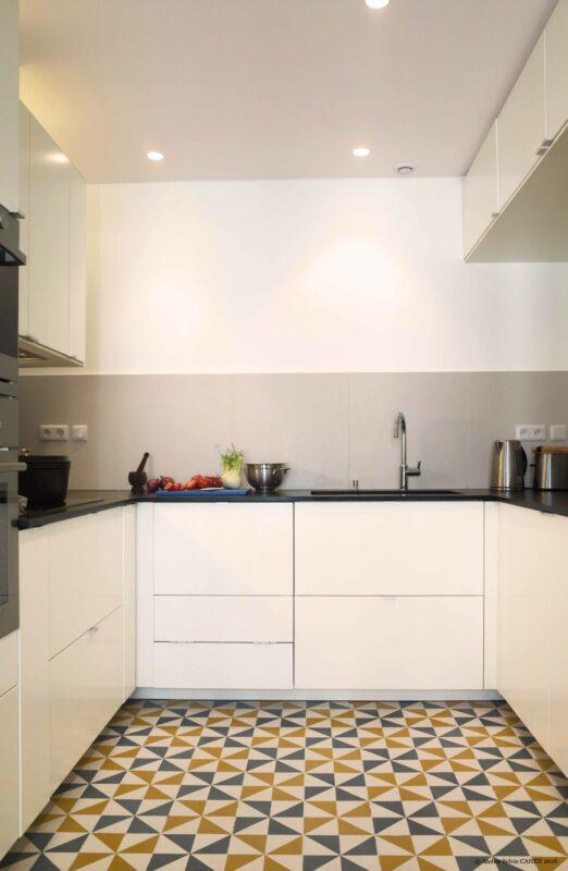 Duplex bleu et jaune. Dans la cuisine, le mélange des couleurs gris / jaune des carreaux ciments « moulins à vent » a été fait sur mesure et a donné la tonalité aux murs et meubles jaunes du reste de l'appartement.