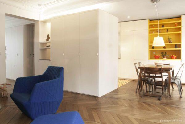 Duplex bleu et jaune. Le meuble structurant sur mesure permet sépare le salon de la partie technique de la cuisine, en laissant entrevoir que la table et le vaisselier.