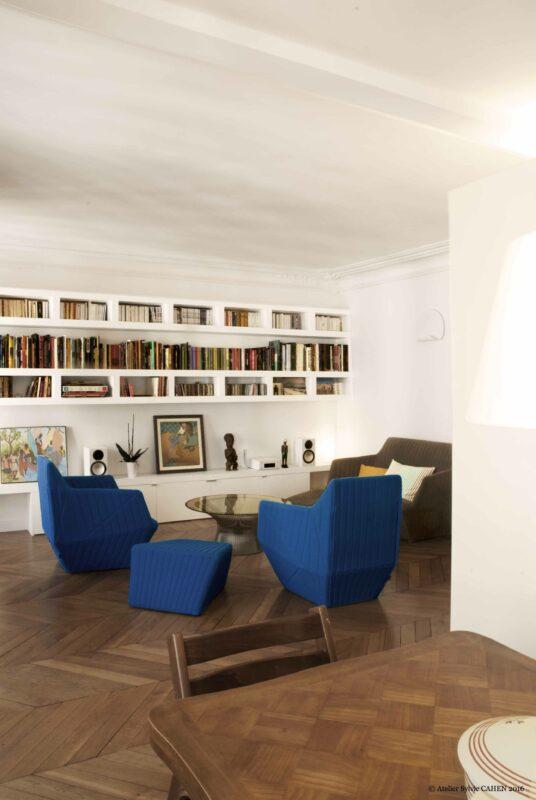 Duplex bleu et jaune. La cuisine s'ouvre sur le salon avec sa bibliothèque sur mesure et ses fauteuils contemporain du bleu qui se retrouve à plusieurs endroits de l'appartement.