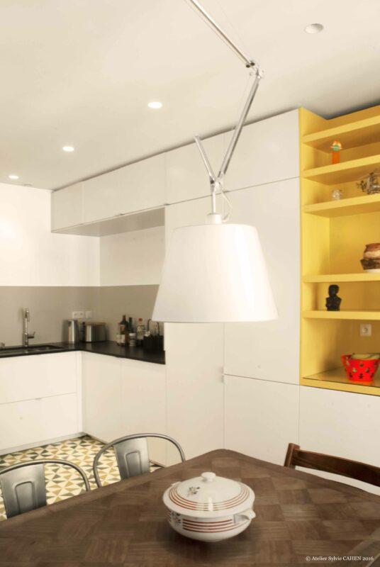 Duplex bleu et jaune. Dans la cuisine, la ligne très contemporaine de l'ameublement sur mesure est complétée par des carreaux de ciment au sol qui permettent de s'accorder au mobilier des années 30 chiné.