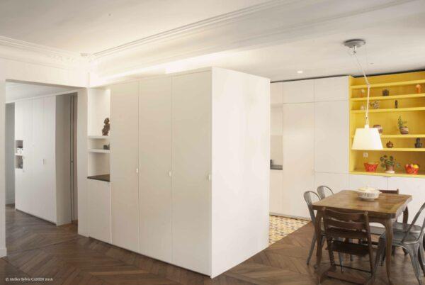 Duplex bleu et jaune. Le grand meuble structurant donne une écriture contemporaine à l'espace. Il met en valeur, par un éclairage indirect, les moulures conservées.