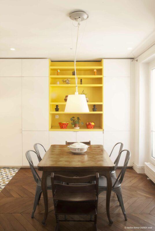 Duplex bleu et jaune. La partie salle à manger des meubles de cuisine abrite une niche jaune, reprenant la couleur des carreaux de ciment.