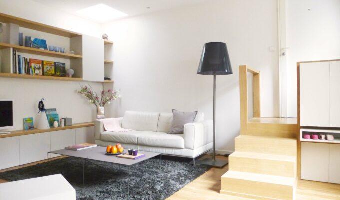 Hôtel particulier. L'escalier sur mesure de l'entrée donne sur un salon chaleureux et contemporain dont les couleurs dominantes sont le blanc et le chêne clair, avec des touches de noirs.