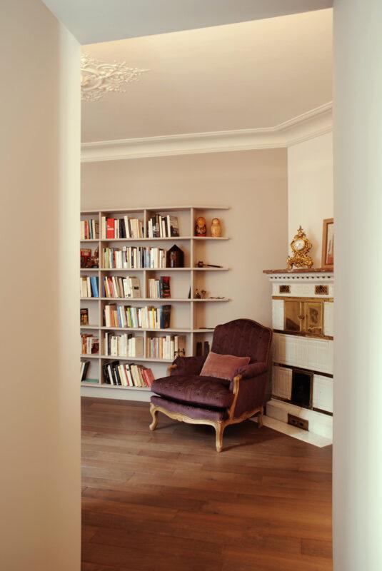 Meuble structurant sur mesure. Depuis l'entrée, le passage dans le meuble traversant, crée un cadrage sur la bibliothèque.