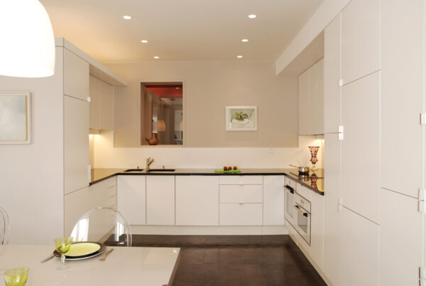 Meuble structurant sur mesure se prolonge en plan de travail de la cuisine, jusqu'à une partie rangement sur le mur de droite.