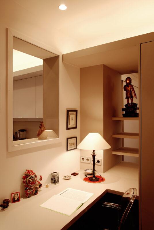 Meuble structurant sur mesure. Dans le bureau, une fenêtre le sépare de la cuisine et des étagères crées un espace ouvert filtré vers l'entrée. Faisant ainsi de ce bureau un espace de vie traversant.