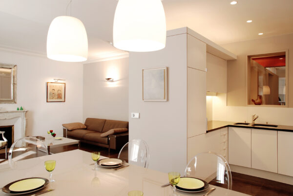 Meuble structurant sur mesure. Le meuble structurant permet de créer un filtre entre le séjour et l'espace technique de la cuisine. A travers une fenêtre intérieure, on peut apercevoir le bureau en second jour.
