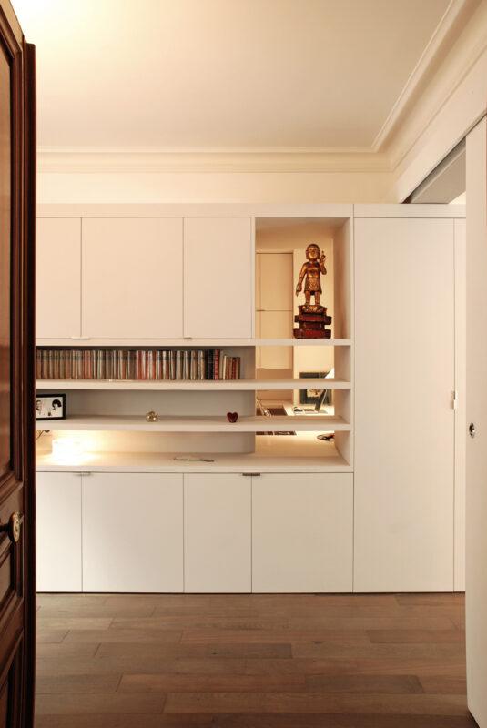 Meuble structurant sur mesure. Depuis l'entrée de l'appartement, le meuble-structurant permet de créer un filtre entre l'espace d'accueil et le bureau.