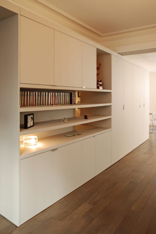 Meuble structurant sur mesure. Le meuble ne va pas jusqu'au plafond pour mettre en valeur les moulures (le soir un éclairage indirect les éclaire).