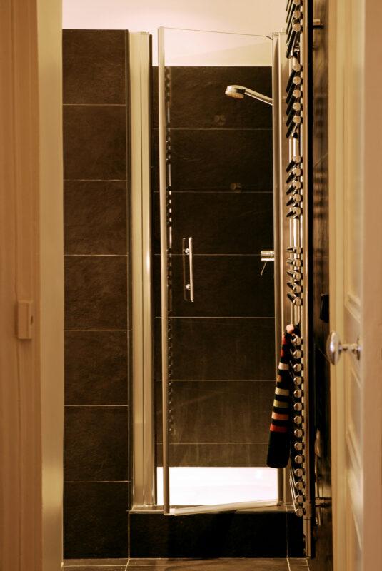 Meuble structurant sur mesure. La douche de la salle de bain, dans des camaïeux de gris et de métal crée une atmosphère nocturne.